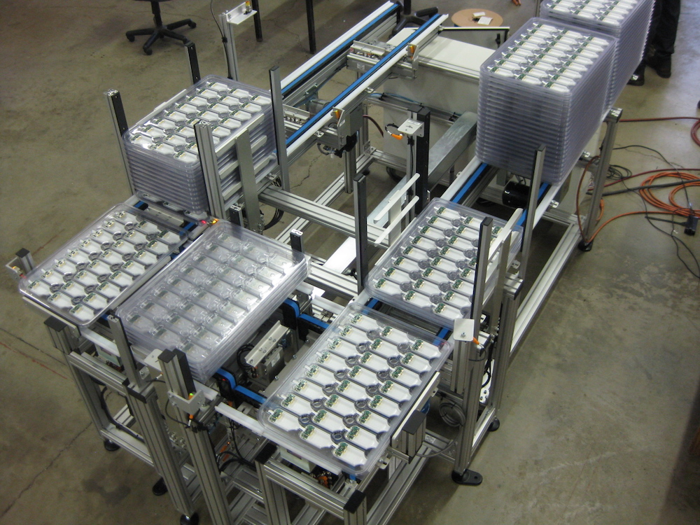 Stackable trays on pallet conveyor